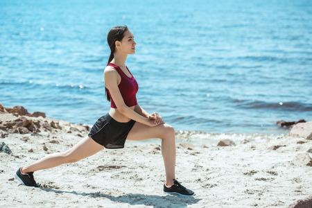 side view of young asian female athlete doing lunges on beach 写真素材