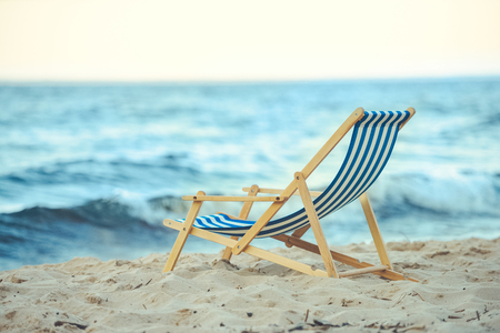 selective focus of wooden beach chair on sandy beach with sea on background