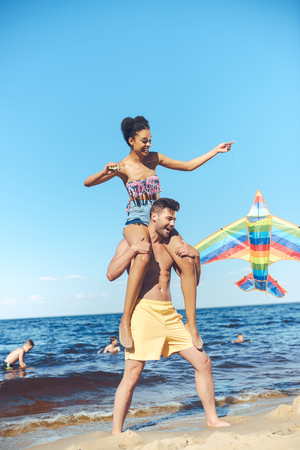 multiracial couple with colorful kite having fun on sandy beach