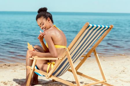 smiling african american woman applying sunscreen lotion on skin while sitting on deck chair on sandy beach Foto de archivo