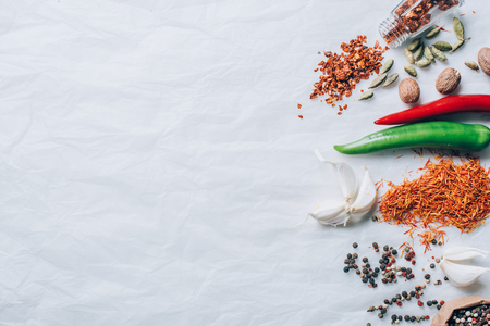 top view of scattered spices on white table