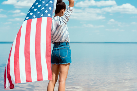 rear view of young woman holding american flag in front of sea, independence day concept 스톡 콘텐츠