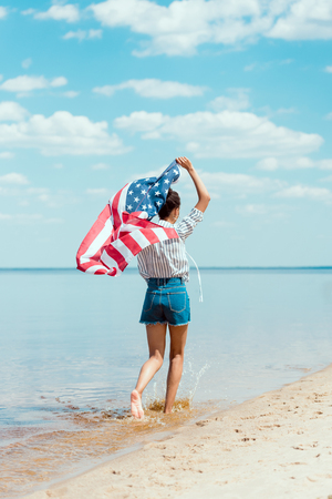 rear view of young woman running in sea water with american flag, independence day concept Banco de Imagens
