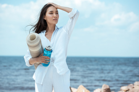 asian young woman holding sport bottle of water and yoga mat by sea