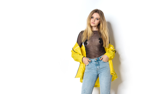 stylish young woman in transparent shirt and yellow jacket on white