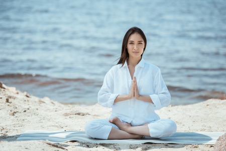 young asian woman in anjali mudra (salutation seal) pose on yoga mat by sea Imagens - 106026362