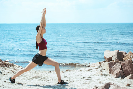young asian sportswoman exercising on beach in front of sea