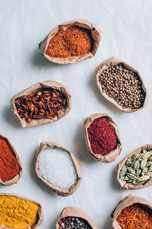 top view of colorful indian spices in paper bags on white table