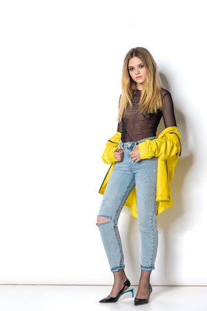 beautiful young woman in transparent shirt and yellow jacket on white Foto de archivo