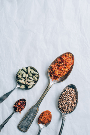 top view of group of spices in spoons on white table Archivio Fotografico