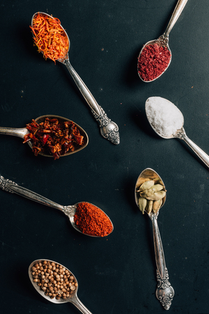 top view of different spices in spoons on dark table