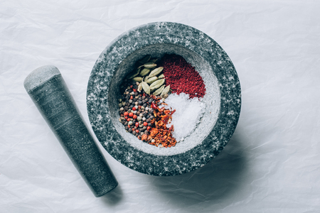 top view of mortar with spices and pestle on white table 写真素材