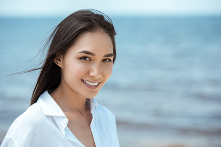 close up portrait of attractive smiling asian woman by sea Stockfoto