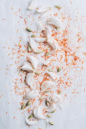 elevated view of scattered garlic and spices on white table