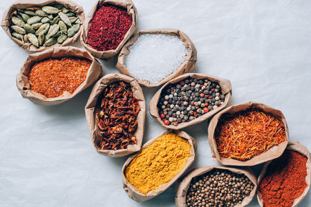 top view of colorful spices in paper bags on white table