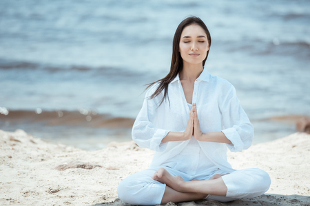 concentrated young asian woman in anjali mudra (salutation seal) pose on beach Standard-Bild