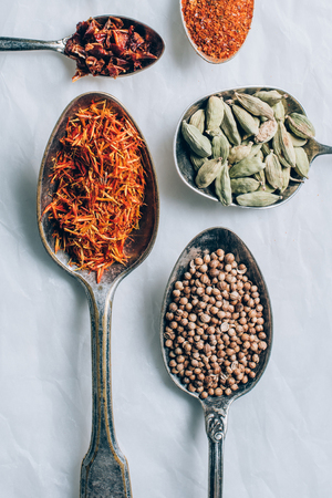 top view of different spices in spoons on white table