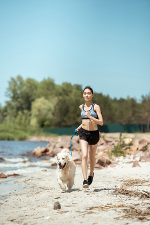 female athlete jogging with dog on beach during daytime Stockfoto