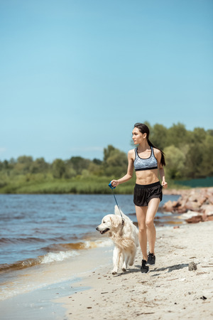 attractive young asian sportswoman running with golden retriever near sea