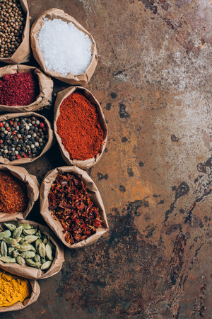 elevated view of colorful spices in paper bags on table Stock Photo