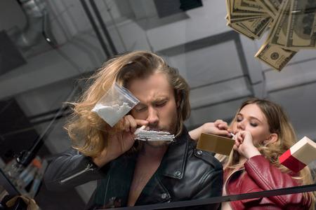vista dal basso attraverso il tavolo di vetro di una giovane coppia di tossicodipendenti sniffare cocaina