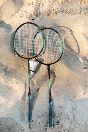 close up view of badminton racquets and shuttlecock lying on sandy beach Imagens - 106049455