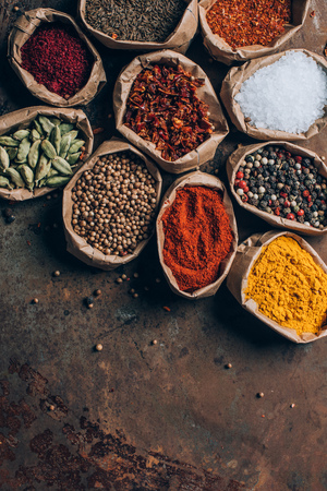 top view of colorful spices in paper bags on table Stock Photo