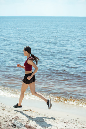 side view of young asian sportswoman running on beach