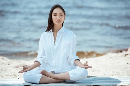 Femme concentrée méditant en ardha padmasana (demi lotus pose) sur un tapis de yoga en mer Banque d'images