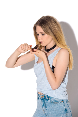 addicted young woman smoking cannabis with pipe on white Stock Photo