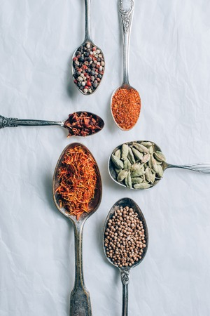 top view of indian spices in spoons on white table