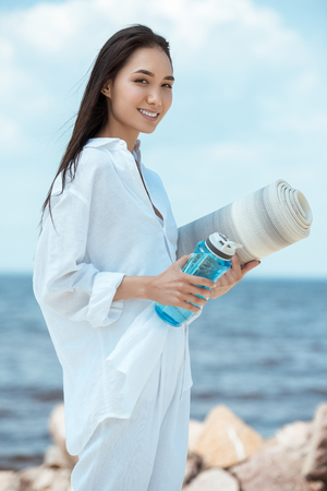 smiling asian young woman holding sport bottle of water and yoga mat on beach