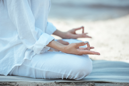 cropped image of woman in ardha padmasana (half lotus pose) on yoga mat by sea