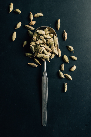 top view of cardamom seeds on spoon and dark table