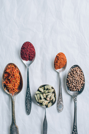 elevated view of different spices in spoons on white table 写真素材