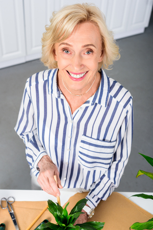 high angle view of happy senior woman smiling at camera while working with houseplants at home