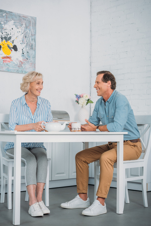 happy senior couple smiling each other while drinking tea together at home