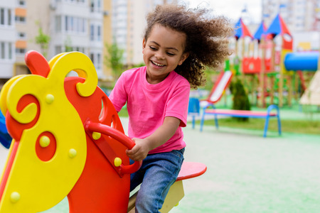 smiling curly african american little child riding on rocking horse at playground