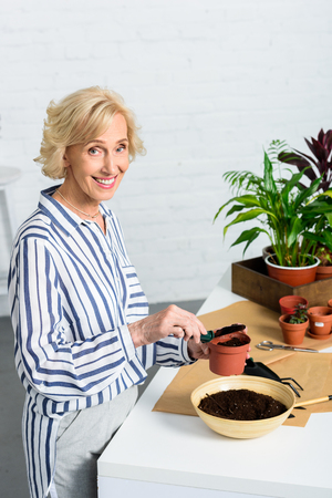 high angle view of happy senior woman holding pot with soil and smiling at camera indoors Stock Photo