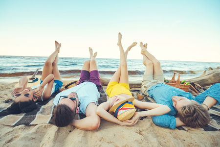 multiracial young people lying on blanket while spending time on sandy beach