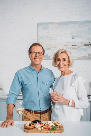 happy senior couple drinking wine and smiling at camera while eating delicious snacks at home Stock Photo