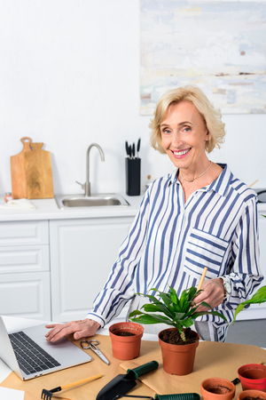 smiling senior woman using laptop and cultivating houseplant at home