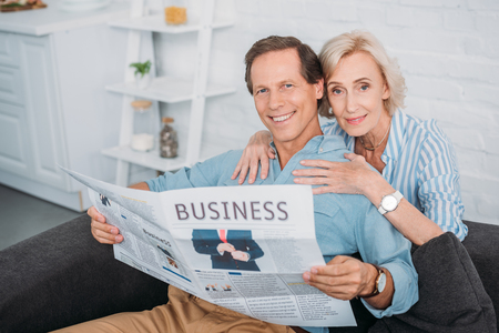 happy senior couple smiling at camera while reading business newspaper at home
