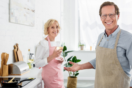happy old man in apron and eyeglasses smiling at camera while wife drinking wine in kitchen
