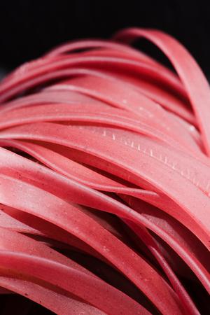 close-up shot of red raw spaghetti on black