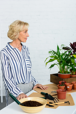 pensive senior woman looking away while cultivating potted plants at home Stock Photo