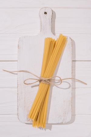 top view of spaghetti tied with thread lying on white wooden cutting board Stock Photo