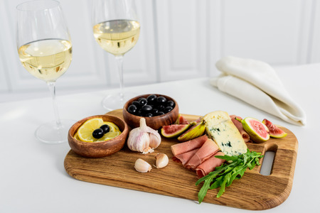 close-up view of delicious snacks on wooden board and glasses of wine on table Imagens - 106050555