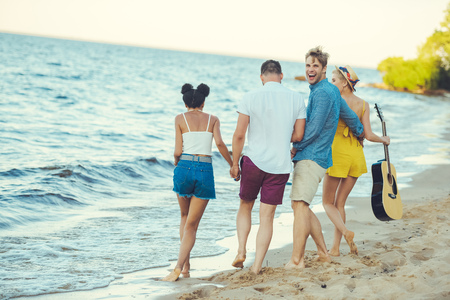 multiethnic group of friends with acoustic guitar walking together by sea Stock Photo