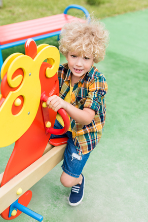 high angle view of happy curly boy riding on rocking horse at playground Stock Photo